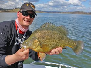 Man Holds up large golden perch
