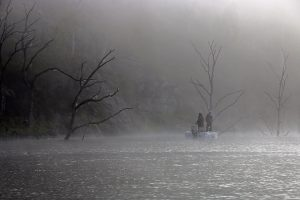 A fishing boat floating in heavy rain and fog.